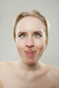 funny portrait of young woman trying to lick her nose, dorky sil